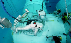 Astronauts training in water for a spacewalk to build the International Space Station