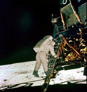 An astronaut climbs down the lunar module's ladder to the moon's surface.