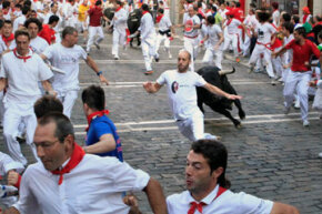 "A fighting bull runs behind participants during the Running of the Bulls in Pamplona, Spain. For eight days, bulls run through the historic heart of Pamplona in this fiesta made famous by the 1926 novel ""The Sun Also Rises"" by Ernest Hemingway."