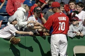 Philadelphia Phillies' Michael Young signs autographs during a workout before a spring training game in Clearwater, Fla.