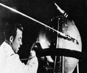 A Soviet technician makes adjustments to the Sputnik satellite.