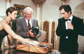 "Bond (Timothy Dalton) meets with Q (Desmond Llewelyn) to receive his case full of gadgets in ""License to Kill."" The gadgets in this film include a camera that fires a deadly laser out of its flash component and a ""signature gun"" that Q has programmed for Bond's use alone."