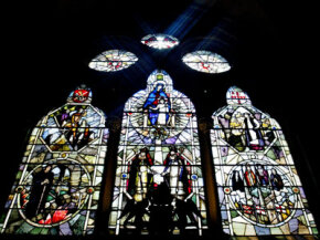 The sun shines through stained glass windows depicting the construction of Southwark Cathedral August 8, 2003, in London, England.