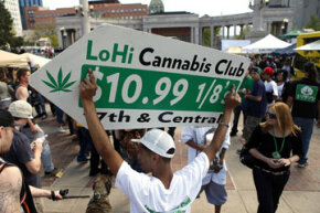 Javier Martinez uses a sign to advertise for LoHi Cannabis Club dispensary at an April 2012 rally for legalized marijuana in Colorado.  In November, voters in that state approved a measure to legalize the drug. See more controlled substance pictures.