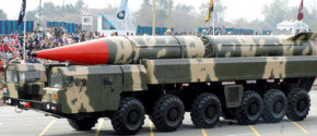 Pakistani spectators watch the Shaheen II long-range missile, capable of carrying a nuclear warhead on its launcher, during the National Day parade in Islamabad on March 23, 2005.