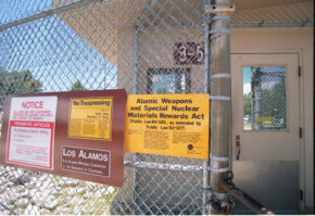 Signs posted on the gated wall around the main technical area of Los Alamos National Laboratory keep visitors informed about security.