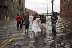 Journalists interview Betty Walsh (C), a local resident of Brooklyn, N.Y. during Hurricane Irene. See more storm pictures.