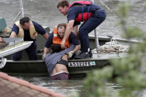 Rescue workers pull a woman from the water who was hanging onto the roof to escape the rising flood waters from Hurricane Katrina.