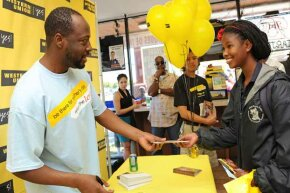 Musician Wyclef Jean (l) passes out $50 Western Union gift cards to fans at an event in Los Angeles. Western Union earnings help to measure migration trends.