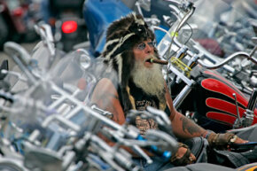 Tiny Carnajan of Minneapolis, Minn., takes a break on his bike at the Sturgis Motorcycle Rally in Sturgis, S.D.