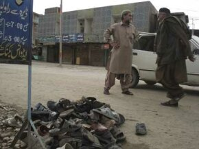 Residents of Dera Ismail Khan, Pakistan, walk past the slippers of those killed and injured in the Feb. 20, 2009, suicide bombing of a Shiite funeral procession.