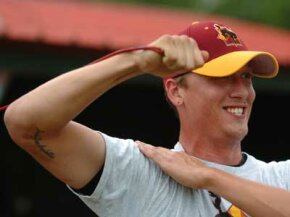 """John Odom of the Laredo Broncos warms up his pitching arm, which bears a scar from Tommy John surgery with a tattoo that reads, in Latin, """"poena par sapientia"""" or """"pain equals wisdom."""""""