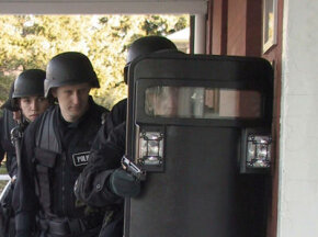 A SWAT team prepares to enter a building during an exercise simulating a hostage situation.  See more police pictures.