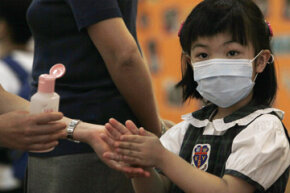 A kindergartener in Hong Kong washes her hands before entering her classroom.