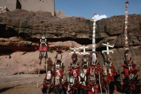 Dogon tribespeople dressed for a funeral. Two people (back row, third from right and all the way on the right) appear to be wearing sirige masks.