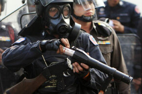 Riot police reload tear gas bullets outside Parliament House on Oct. 7, 2008, in Bangkok, Thailand.