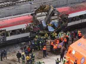Rescue workers cover up bodies following a 2004 train bombing in Madrid, Spain, March 11, 2004. The terrorist attack killed more than 170 commuters and wounded more than 500.