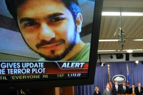 An image of terror suspect Faisal Shahzad flashes on a TV screen as U.S. Attorney-General Eric Holder (C) and other officials hold a briefing regarding the investigation into the Times Square attempted bombing.