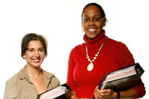 Armed with binders containing the entire script for the 79th Annual Academy Awards (2007), script supervisors Jenny Stanley (left) and Shannon Smith pose for a photo.