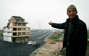 Luo Baogen points to his house which his provincial government built a road aound when he would not sell it to them. Tired of the traffic noise, he later sold his house to the government for slightly more money than he had orginally been offered.