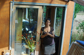 Lulu (no last name given) stands outside one of the two tiny houses she shares with her daughter. This one is used as a bedroom and office. The other has the kitchen and living area.