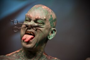 """Erik Sprague (aka """"The Lizardman"""") shows off some of his body modifications (split tongue, subdermal implants and sharpened teeth among others) at the Copenhagen Ink Festival in 2011."""