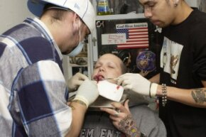A man performs a tongue-splitting procedure on a 25-year-old tattoo artist in New York in 2003 – before it became regulated in 2004.