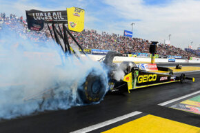 The GEICO Top Fuel dragster performs a smoky burnout with driver Richie Crampton at the wheel.