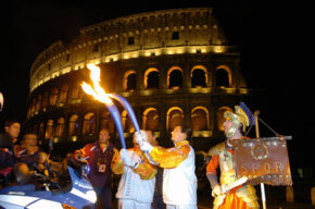 During the 2006 Torino Olympic Torch Relay, a torchbearer passes the flame to a fellow torchbearer.