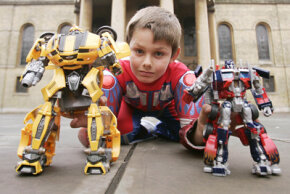 A boy plays with Transformers action figures. See more toy pictures.