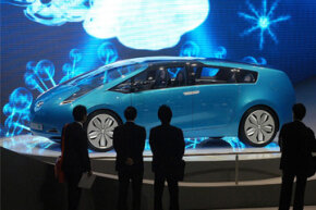 Visitors look at the new Toyota Hybrid X Concept car during a media preview day at the 77th Geneva International Motor Show in Geneva, Switzerland, on March 7, 2007. See more hybrid car pictures.