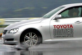 The Toyota Mark X is driven to demonstrate its VGRS safety system. VGRS, which stands for variable gear ratio steering, controls steering, braking and turning of the tires to reduce spinning and skidding when braking and turning on slippery surfaces.