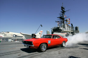 A Chevrolet Camaro burns its tires alongside a Navy fighter jet during a demonstration on the flight deck of the USS Midway in San Diego, Calif.