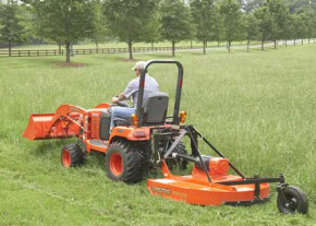 A lawn tractor with accessories attached.