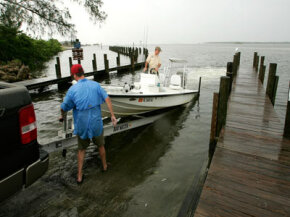 Two Floridians load their boat onto a trailer as they wait for Hurricane Wilma. Trailer bearing protectors should keep the boat's hubs clean in inclement weather.