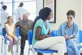 A triage nurse talks with a patient in a waiting room. After finding out the symptoms, the nurse determines how immediately the patient must be seen.