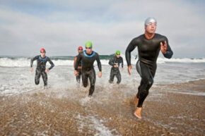 Triathletes dashing out of the surf, on their way to the biking portion of the race. The order of triathlons is generally swim/bike/run.