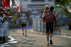 A triathlete races with his young daughter during the 1998 Ironman triathlon in Hawaii. Families traveling to triathlons don't have to get this involved unless they want to.