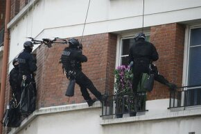 Members of a French police intervention unit take positions while a drone flies outside a building where a man is barricaded with his children and threatening their safety.