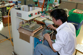 Athletic shoe assembly: After hot melt film has been applied to synthetic suede, the film is pressed.