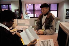 An office clerk peruses an application for unemployment in New York while the applicant waits. There are some tax breaks to offset the taxes on your unemployment checks.