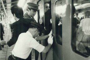 An oshiya (pusher) is needed to cram passengers into a commuter train during rush hour in crowded Tokyo, as seen in this 1987 photo.