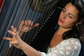 A music-thantologist uses harp music to soothe a dying patient during his or her final moments.