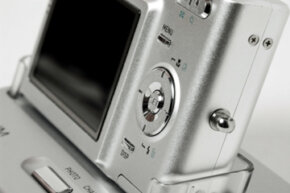 A digital camera in a dock, ready to transfer photos. See more cool camera stuff pictures.