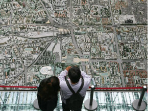 At the Planning and Exhibition Hall in Beijing, a pair of visitors examines a scale model of the city.