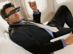 Advertisments tout that video glasses are perfect for long plane rides. This guy sure seems to be enjoying them.
