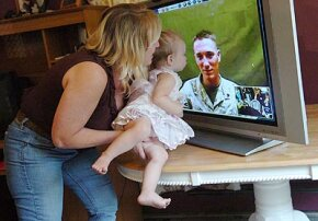 Autumn Lewis, 19 months old, gets a lift so she can kiss dad, Corporal Barry Lewis, in Iraq.