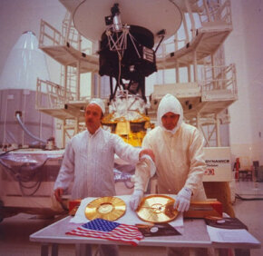 """Sounds of Earth"" gold-plated record and U.S. flag prepared for storage aboard Voyager 2 spacecraft, with project manager John Cassini (left), at Kennedy Space Center."