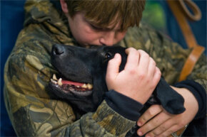 Brady Rusk, 12, hugs Eli, the bomb-sniffing military working dog his older brother Marine Pfc. Colton Rusk, worked with before being killed in action in Afghanistan.
