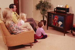 A family sits in their living room watching television. Take a look at TV evolution pictures to see popular shows and TV styles through the decades.